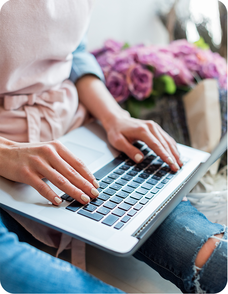 Female in a sweater and jeans working on a laptop