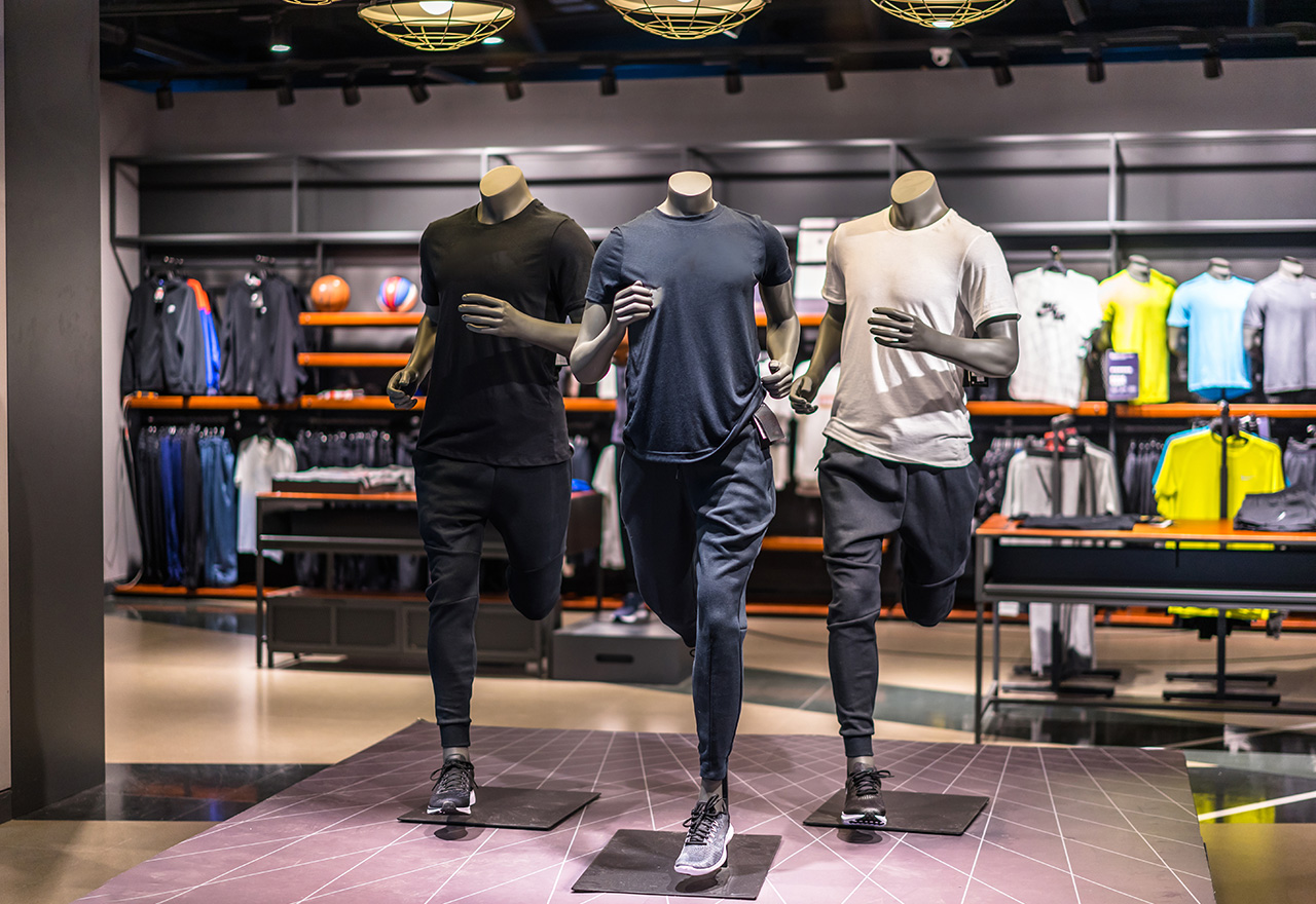 Three male mannequins dressed in athletic wear running in a store