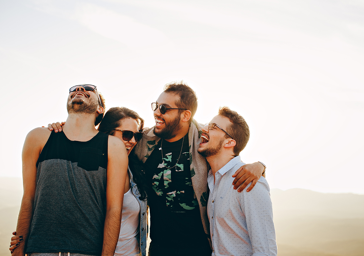 Four millennials laughing together