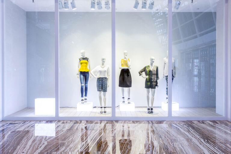 Five female mannequins behind a retail display window