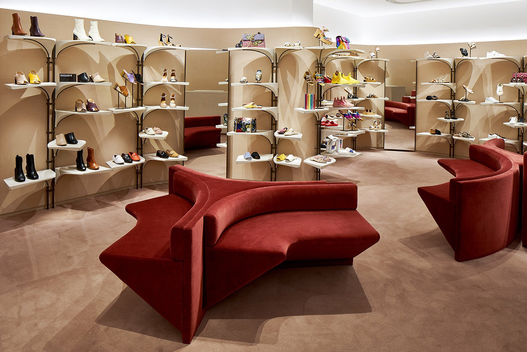 Kurt Geiger store footwear wall with big red couches
