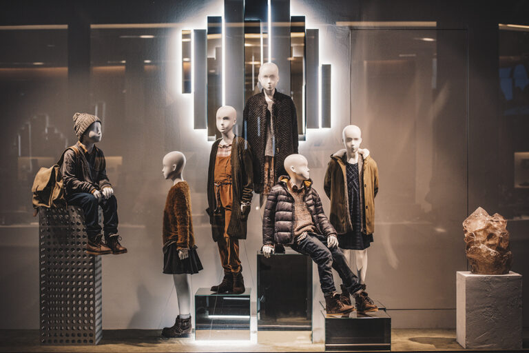 Window display of six child mannequins wearing fall apparel