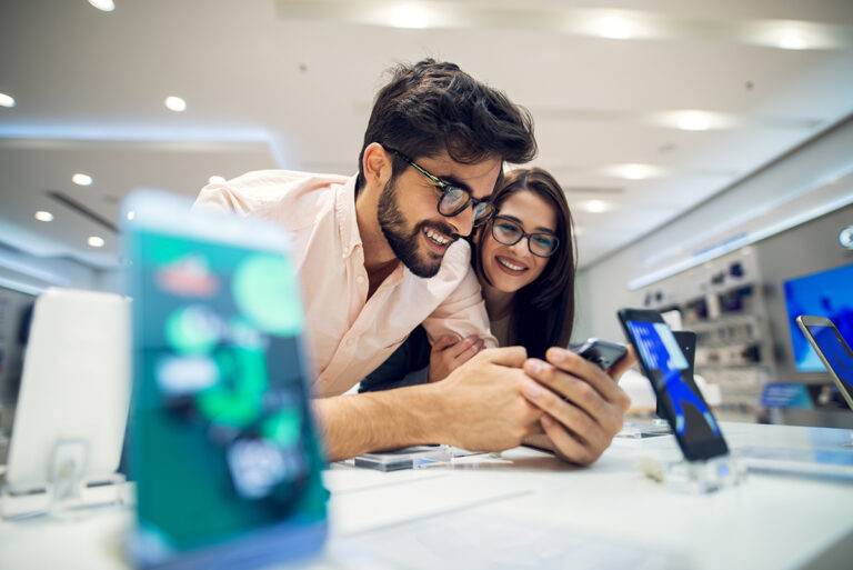 Retail employees looking at a phone display in a telecommunication store