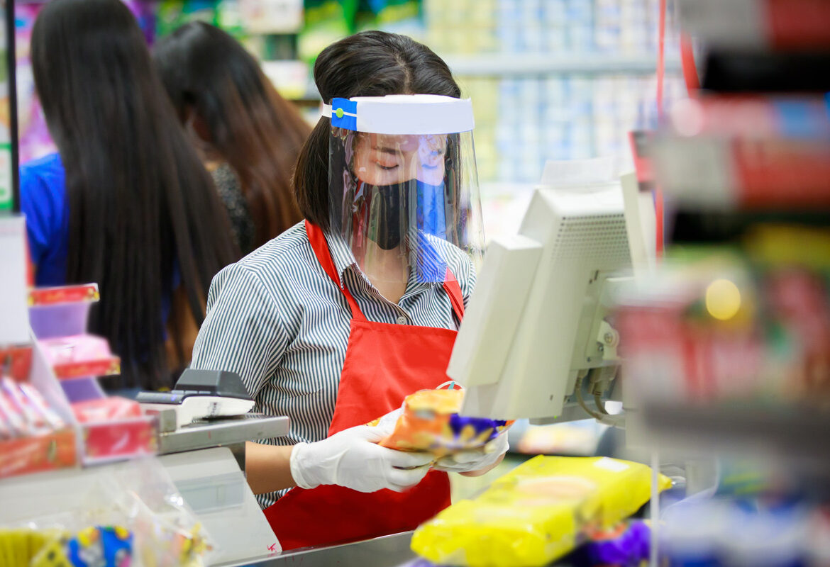 Grocery store associate wearing a COVID-19 face mask working in a reopened store