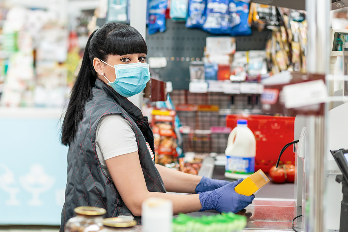 grocery store associate wearing a blue face mask during COVID-19