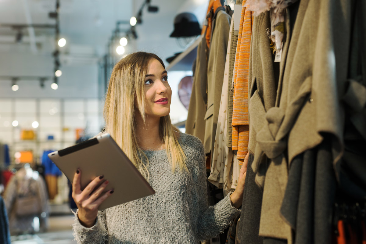 Female store associate referencing product information on a tablet in a clothing store