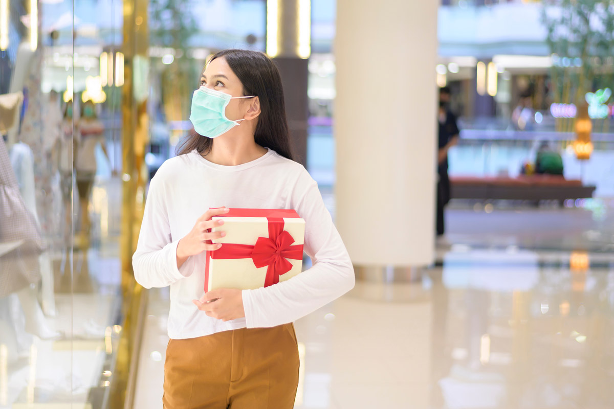 woman wearing a mask holding a present while shopping in a mall