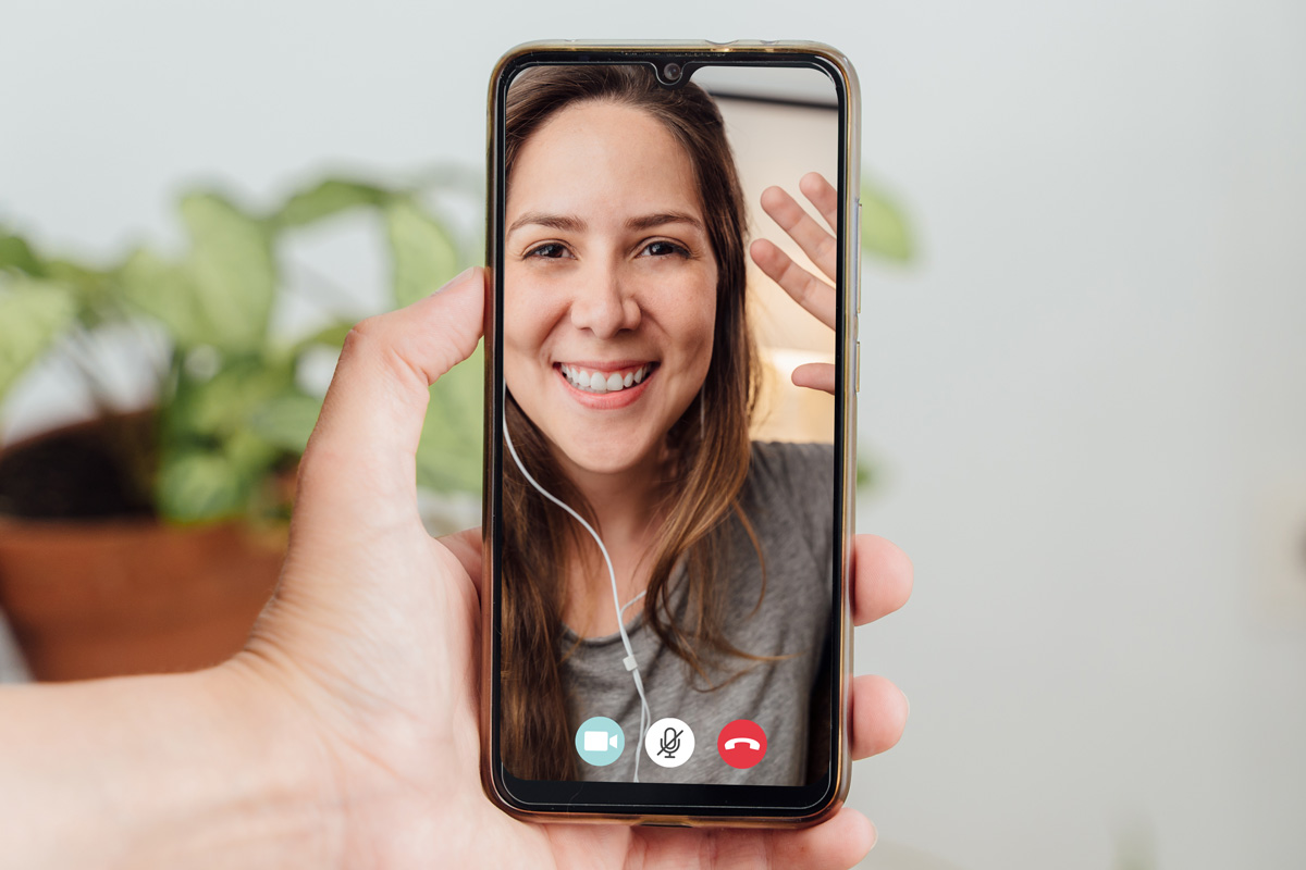 Person on a video call with a smiling and waving woman