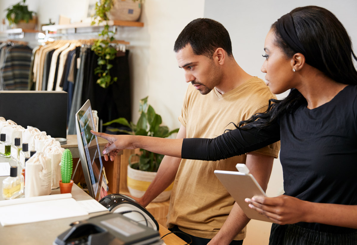 woman pointing at a computer while training an employee in a store