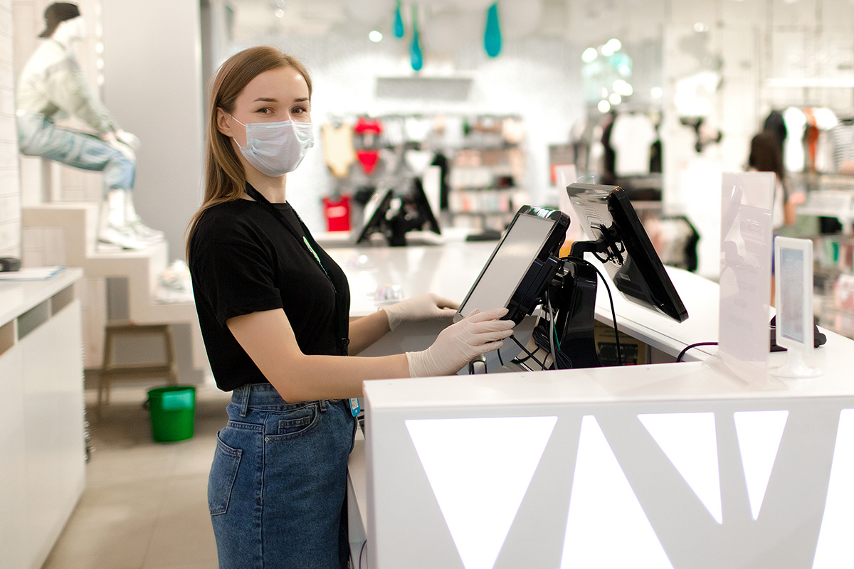 young woman wearing a face mask working in a department store