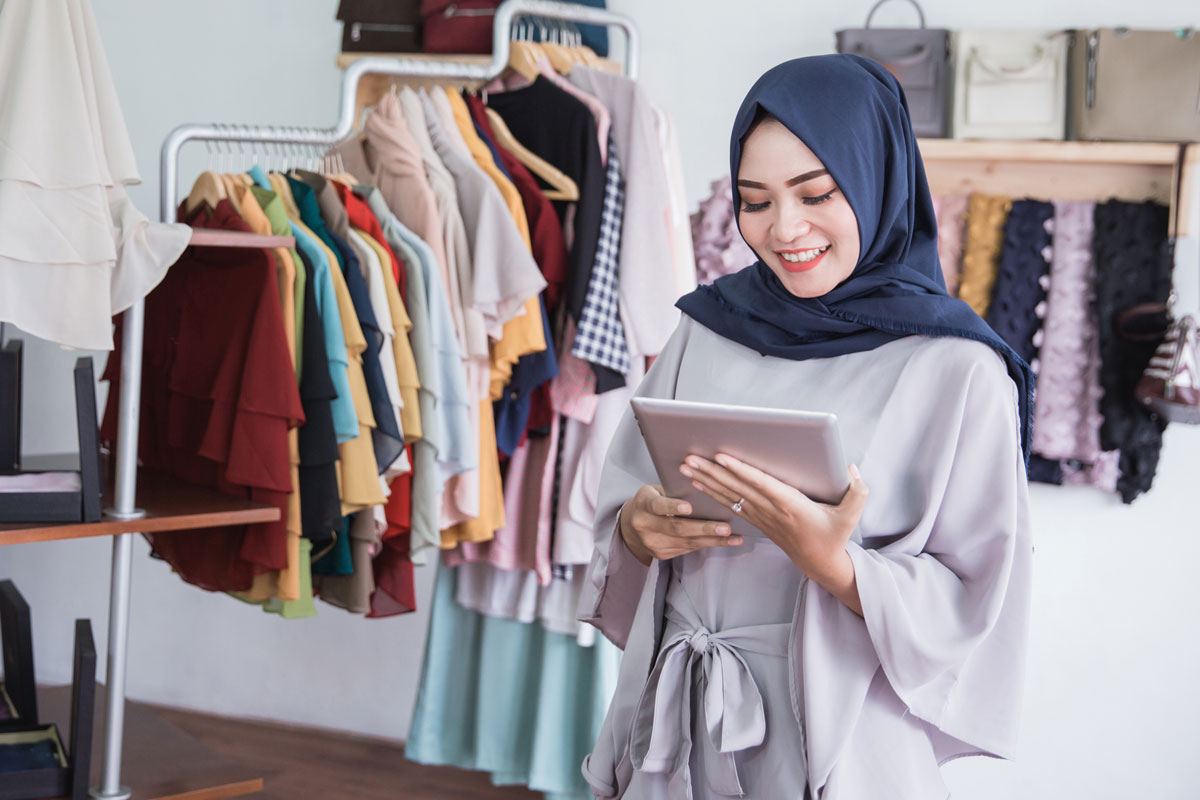 woman wearing a hijab using a tablet in a clothing store