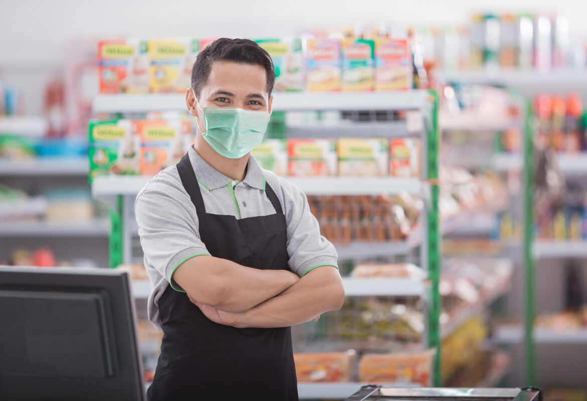 retail employee standing with arms crossed and smiling while wearing a green face mask