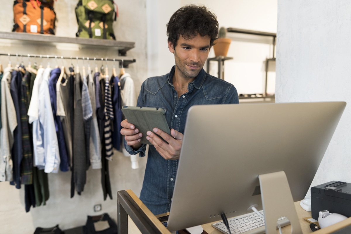 apparel store manager holding a tablet while staring at store operations software on his computer
