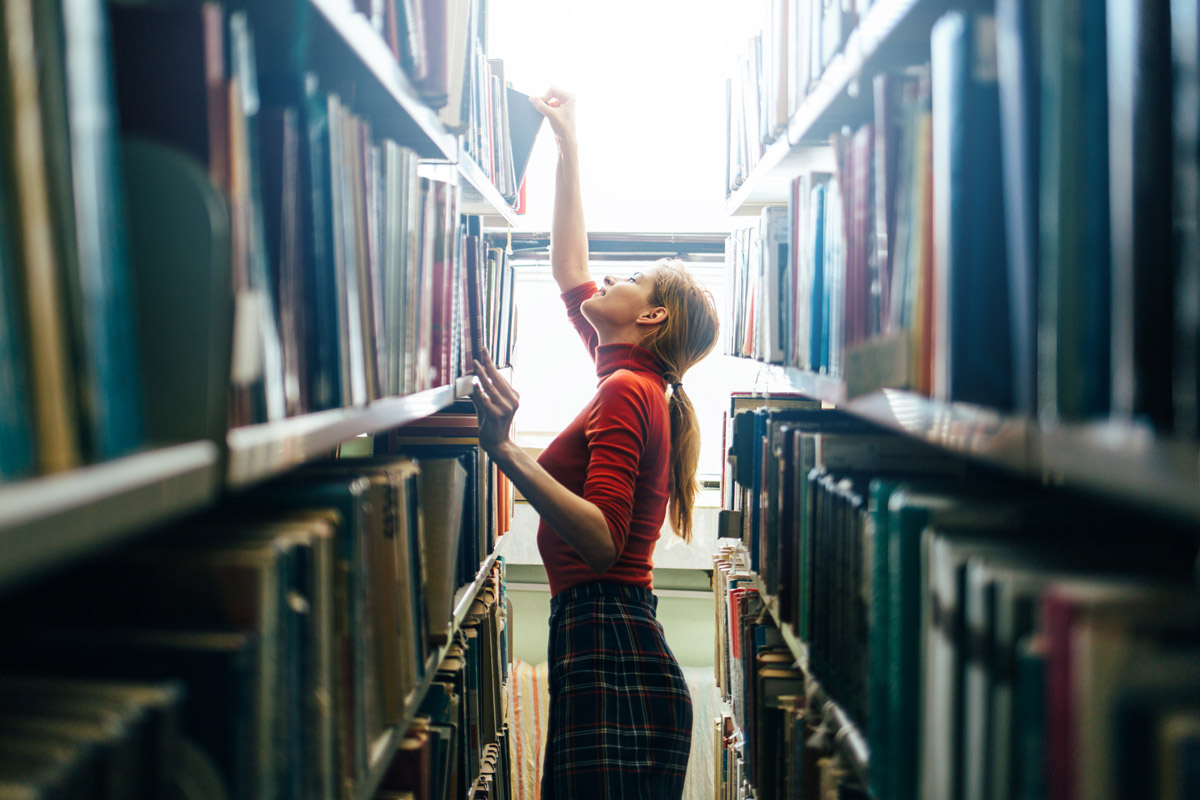 Young female retail professional reaching for a book on retail management in a library