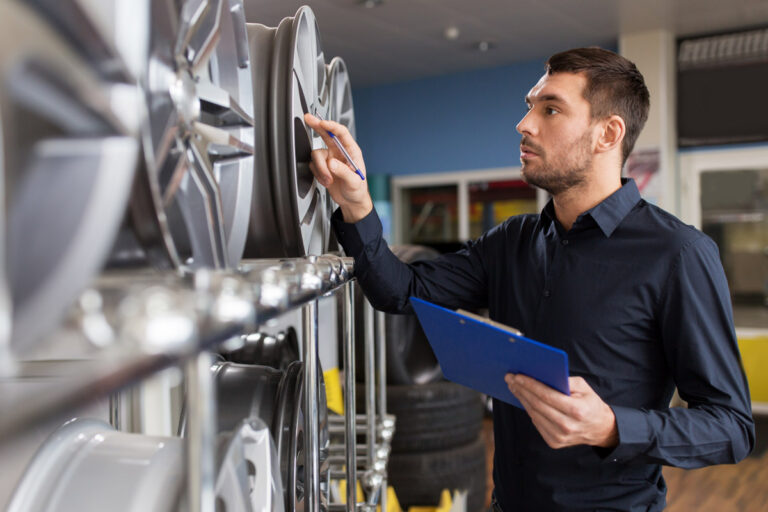 Male retail worker looking at car rims while holding a clipboard