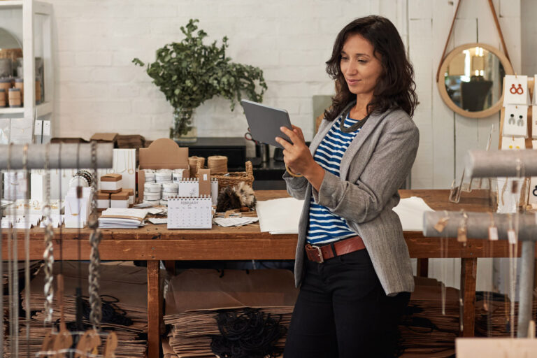 Female store associate using a retail task management system on a tablet in a boutique